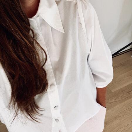 Hvid kort skjorte med pufærmer og volume, samt et feminint snit